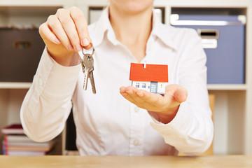 Makler hält Haus und Schlüssel