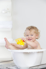 Smiling baby sitting in bathtub holding rubber duck