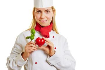 Junge Köchin hält Herz und Basilikum