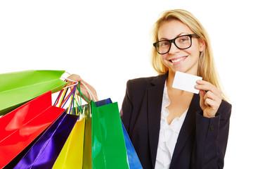 Frau mit Einkaufstüten zeigt Kreditkarte