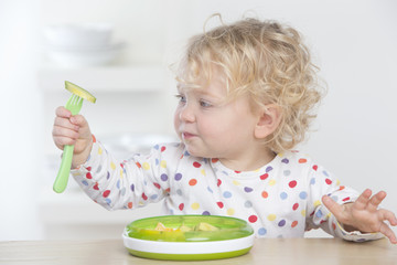 Curious baby eating avocado with fork