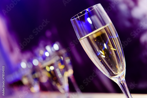 Tuinposter Alcohol Champagne glass in nightclub neon lilac, blue, purple lights