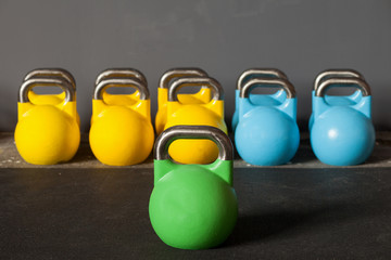 colorful kettlebells in a row in a gym - focus on the front kett