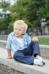 curly-haired boy in shirt smiling