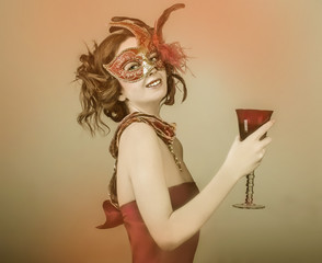 Portrait of woman in mask with glass of wine.