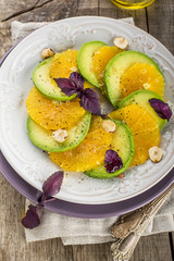 Appetizer of avocado, orange with purple basil and hazelnuts