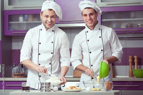 Leinwanddruck Bild Tiramisu cooking concept. Portrait of two smiling men
