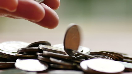 Business man hand dropping money coins