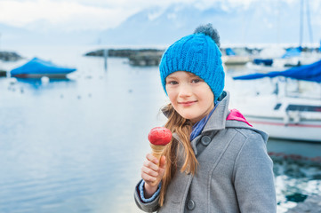 Adorable little girl eating ice cream outdoors