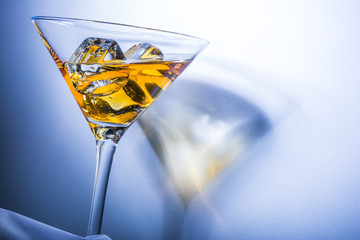 Orange liqueur into a martini glass. Multicolored reflections.
