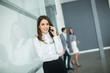 Young woman in office with mobile phone