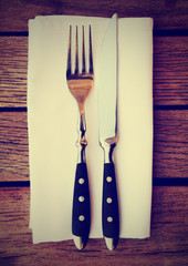 Fork, knife and napkin on table, toned