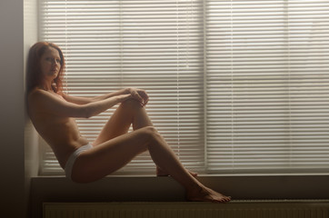 A woman on the windowsill in diffuse light