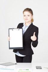 youbg businesswoman showing blank clipboard