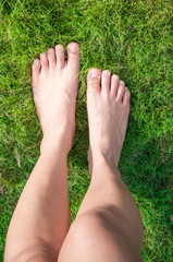 Woman feet over green grass.