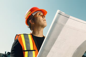 Construction workman outside with plans