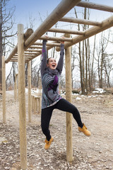 Pretty girl training on monkey bars obstacle