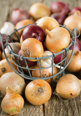 red and yellow onion in an iron basket on wooden surface