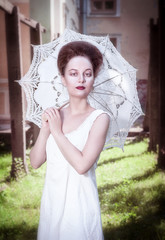 Beautiful young gothic woman in white shirt with umbrella