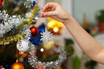 Woman hand hanging christmas decoration