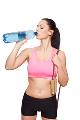 Young woman in sportswear drink water and holding jump rope