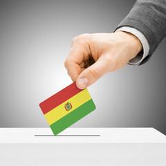 Voting concept - Male inserting flag into ballot box - Bolivia