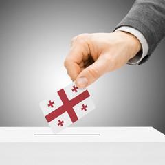 Voting concept - Male inserting flag into ballot box - Georgia