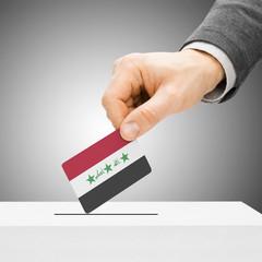Voting concept - Male inserting flag into ballot box - Iraq