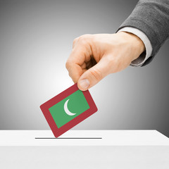 Voting concept - Male inserting flag into ballot box - Maldives