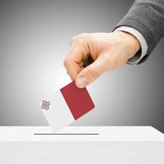 Voting concept - Male inserting flag into ballot box - Malta