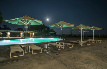 Pool, sunbeds and umbrellas at night