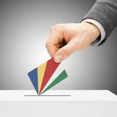 Voting concept - Male inserting flag into ballot box - Seychelle