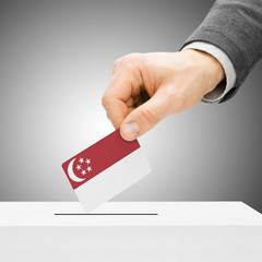 Voting concept - Male inserting flag into ballot box - Singapore