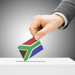 Voting concept - Male inserting flag into ballot box - South Afr