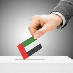 Voting concept - Male inserting flag into ballot box - United Ar