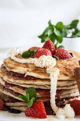 White plate full of pancakes with raspberries strawberries blueb