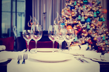 Place setting with Christmas tree in background, toned