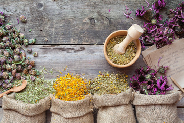Healing herbs in hessian bags, wooden mortar and recipes, herbal