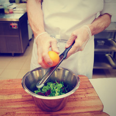 Chef is zesting orange in bowl with salad, toned