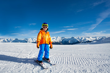 Small boy wears ski mask and stands on ski-track