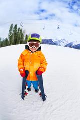 Cute boy wearing ski mask and helmet stands