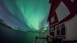Aurora Borealis reflected on a lake with boat house