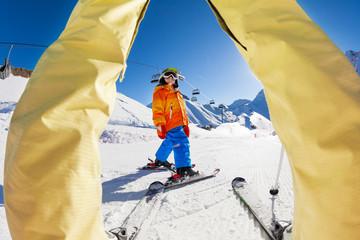 Skiing boy view between the legs of grown-up