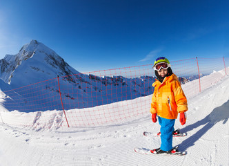 Small boy skiing and standing near fence on snow