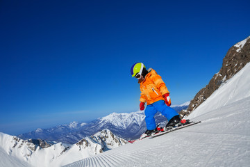Brave small boy skiing alone on mountain slope