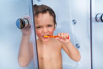 Little cute boy use toothbrush in shower cabin