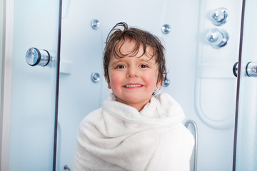 Little boy after shower covered in towel smile