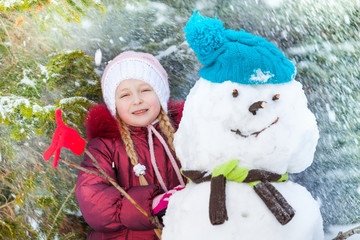Portrait of a girl with snowman and snow flakes