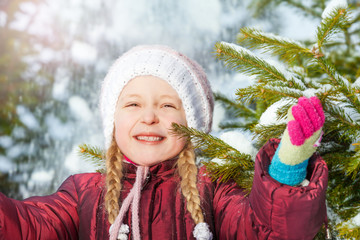 Portrait of happy girl with fir tree and snow