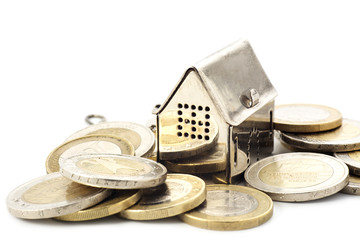 real estade background, little house in a heap of coins isolated